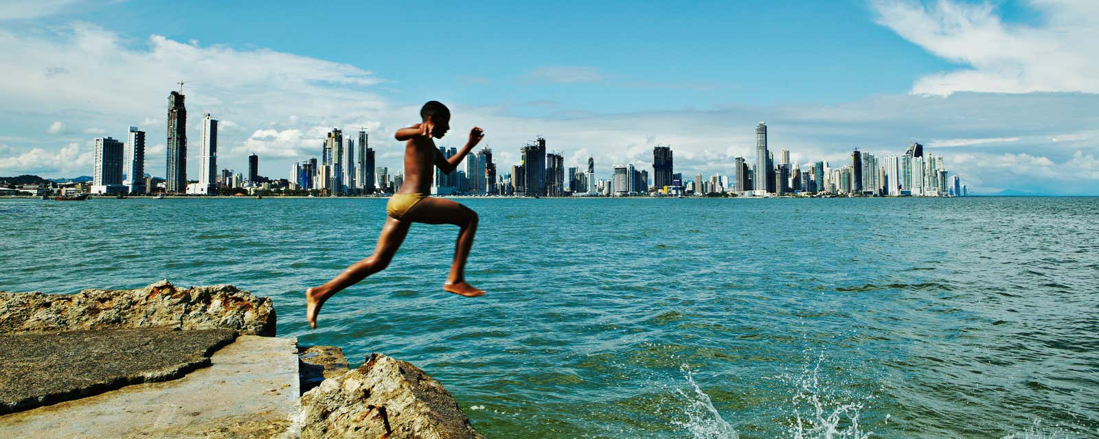 A young boy jumps into the bay of Casco Viejo, Panama City.