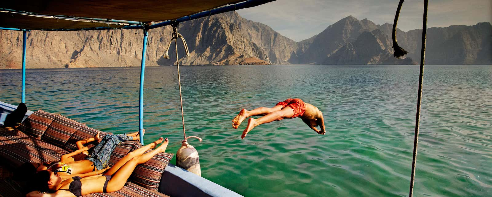 A man diving from a boat on the Musandam Coast, Oman.
