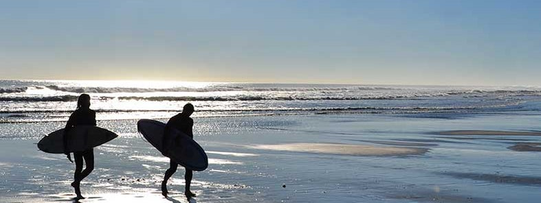 Surfers at Piha Beach by Simon Clancy