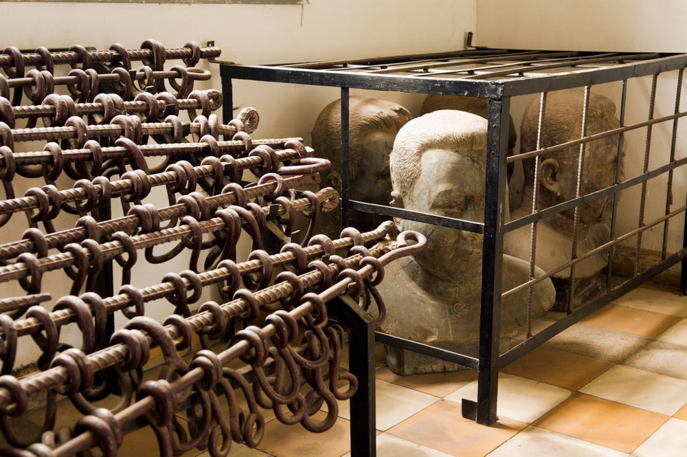 Rack of leg shackles and busts of Pol Pot at Tuol Sleng Museum.