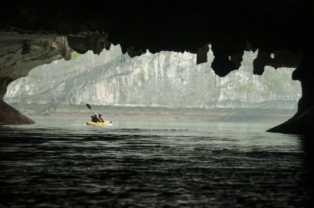 Kayaking through a rock arch at Lan Ha Bay.