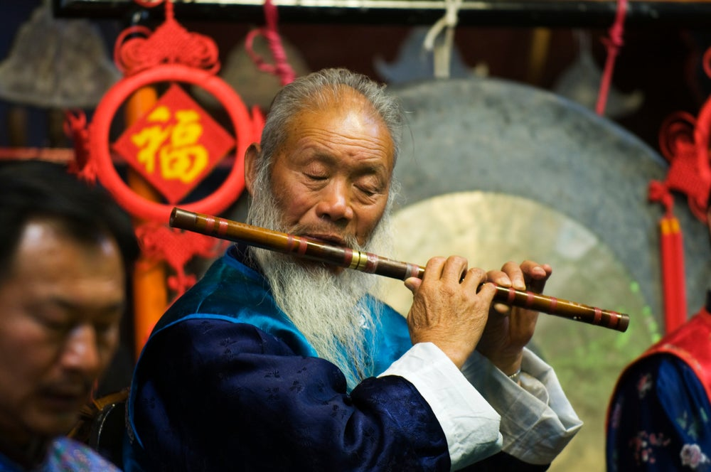 Naxi Orchestra musician playing the flute.