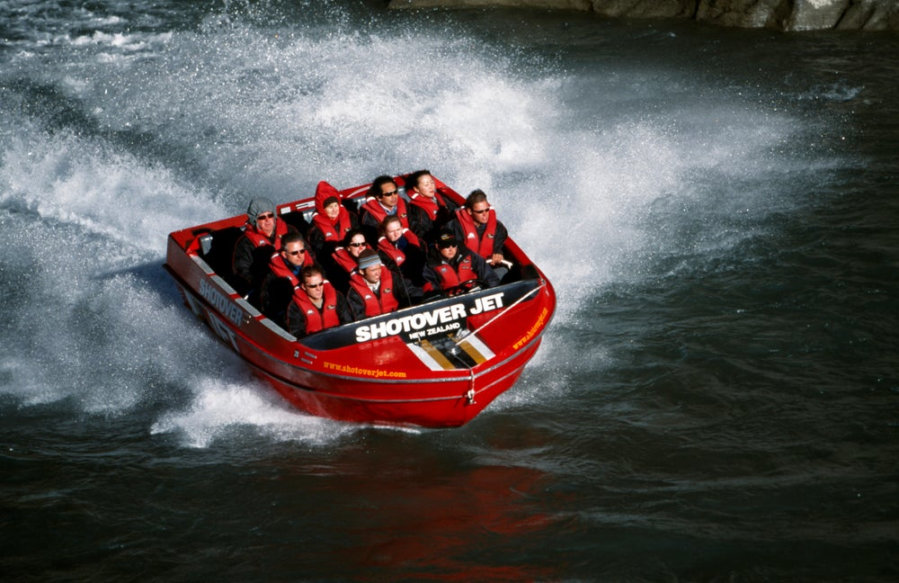 Tourists ride the Shotover Jet on the Shotover River.