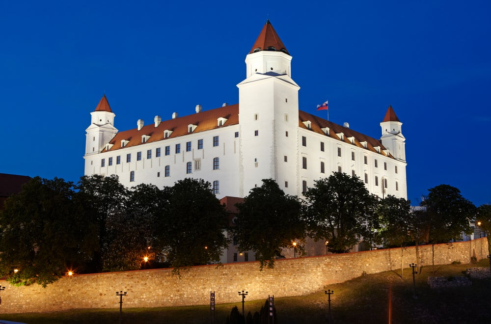 Bratislava Castle illuminated at night.