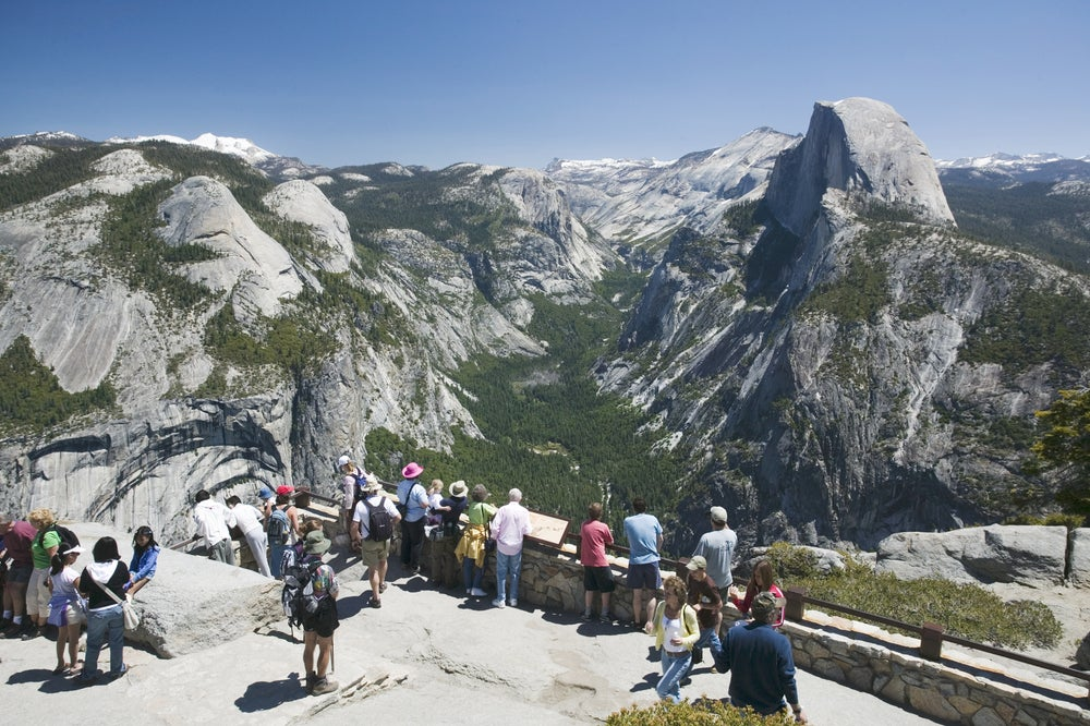 Overhead of park visitors at Glacier Point with Half Dome in background.