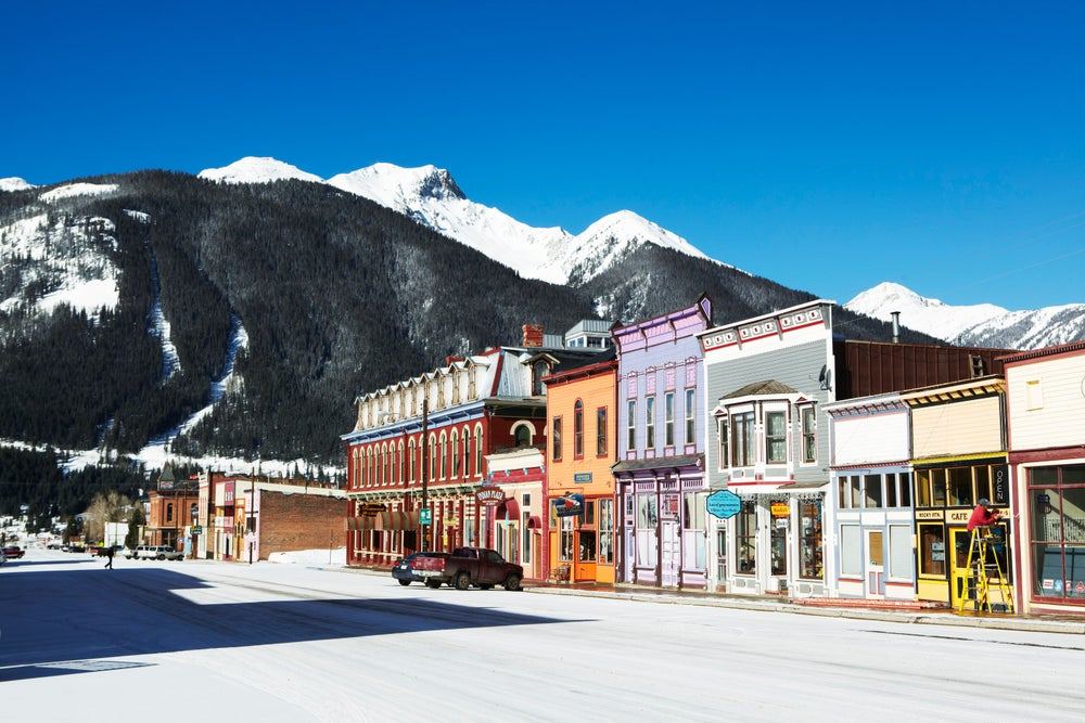Wooden Victorian era shopfronts on Greene Street with San Juan Mountains in background.