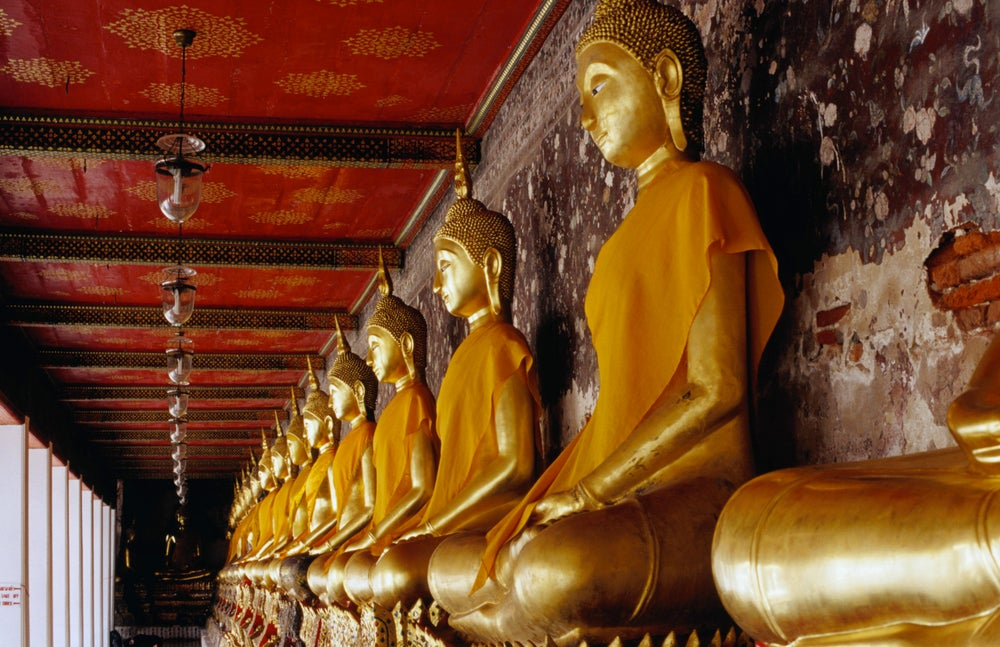 Buddha statues lining walls of compound of Wat Suthat, Phra Nakhon.