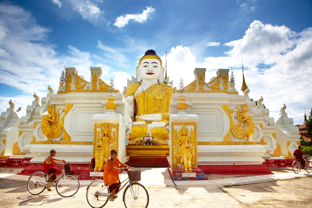 Novice monks cycling past 26-foot high sitting Buddha at Yan Aung Nan Aung Hsu Taung Pyi Pagoda near Inle Lake.