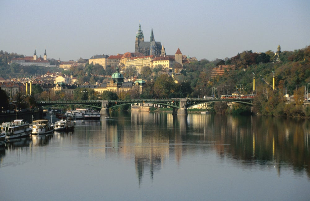 Prague Castle and Strahov Monastery reflecting on Vltava River.