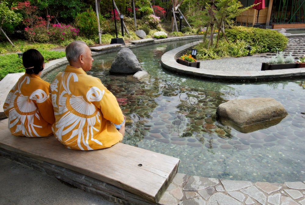 Elderly couple in kimonos dipping feet in ornamental foot bath, Oedo Onsen Monotogari, Odaiba.