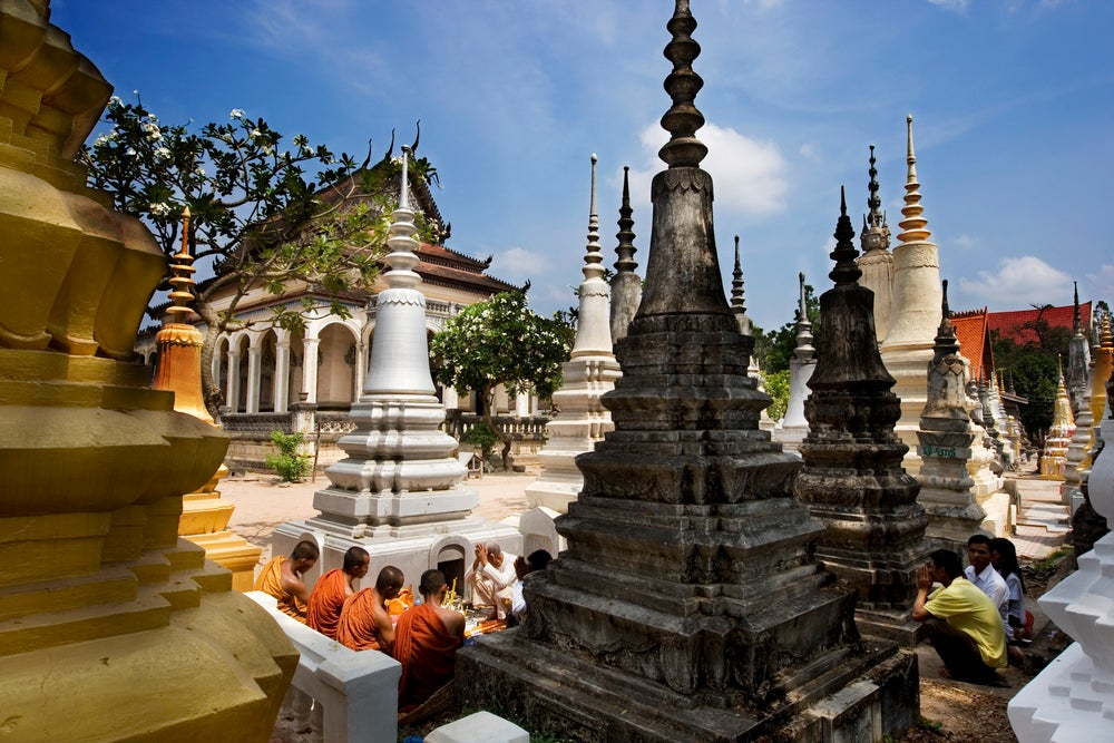 Monks and laypeople sitting amidst stupas at Wat Bo.