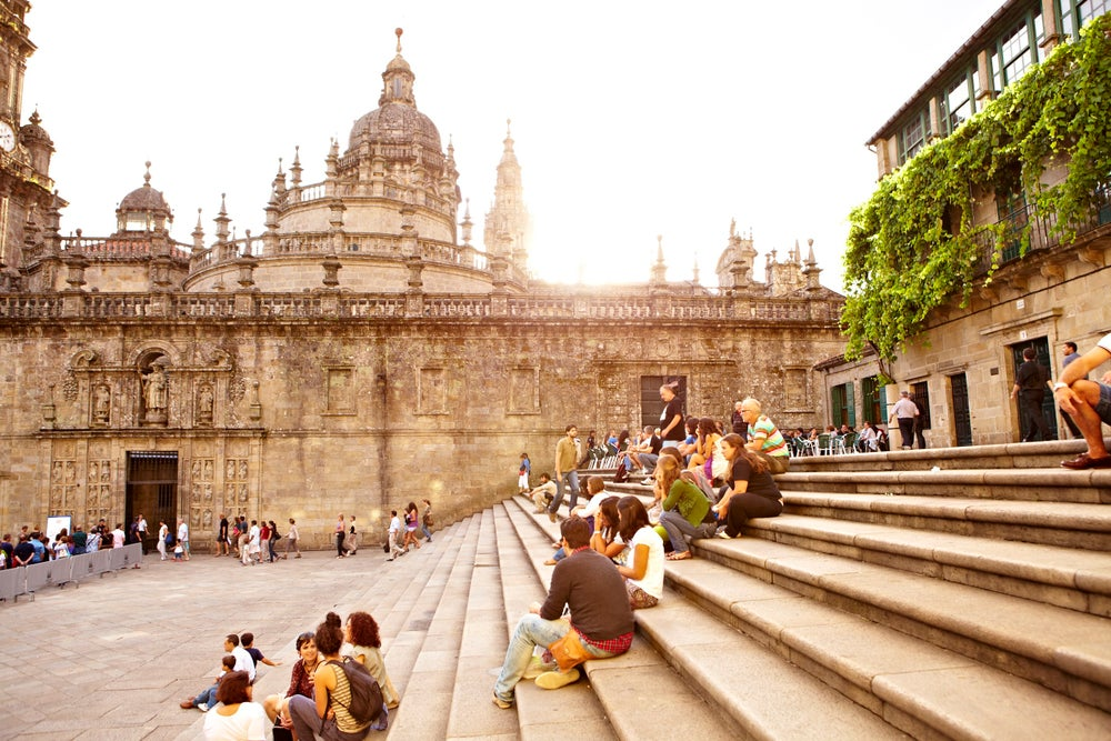 Visitors sitting on steps outside Santiago de Compostela Cathedral.
