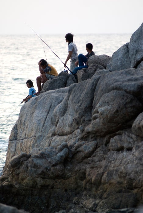 Fishing from rocks at Surin Beach.