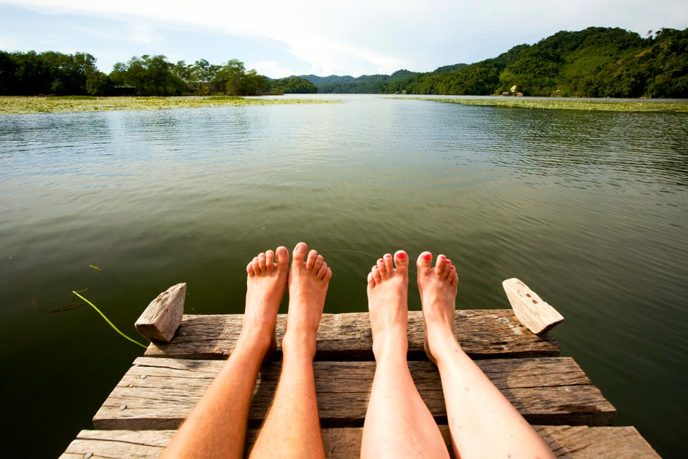 View of couple's feet sitting on river jetty.