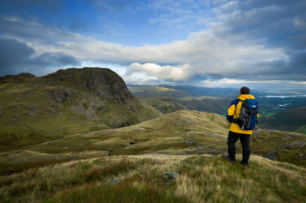 Hiker standing on Loft Crag looking towards Harrison Stickle, Langdale Pikes.