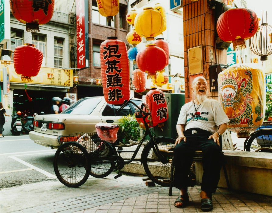 Man sitting outside his traditional lantern workshop.