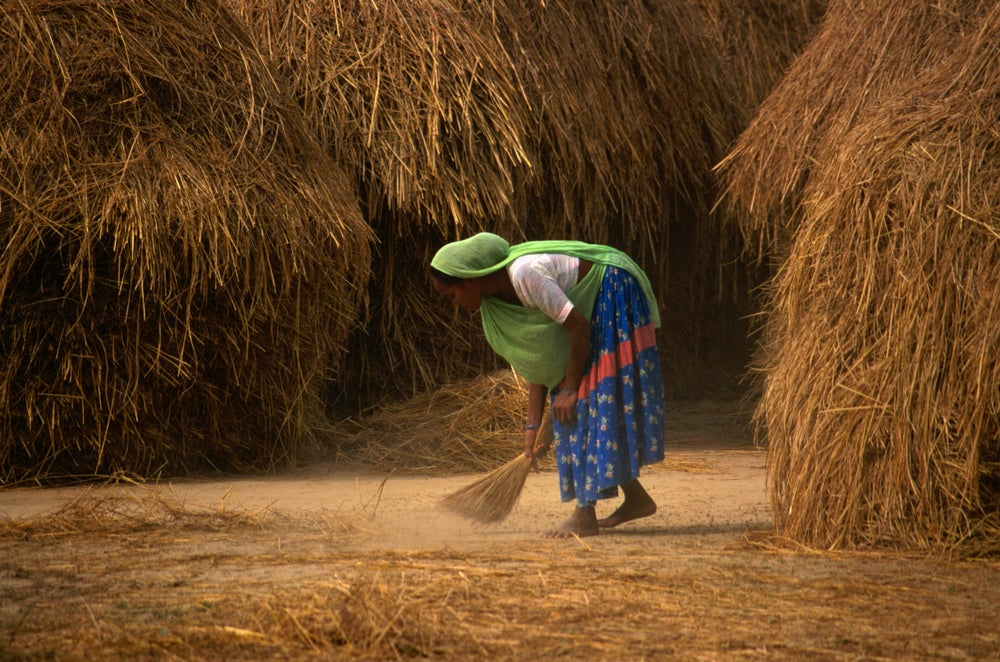 A Tharu woman sweeping.