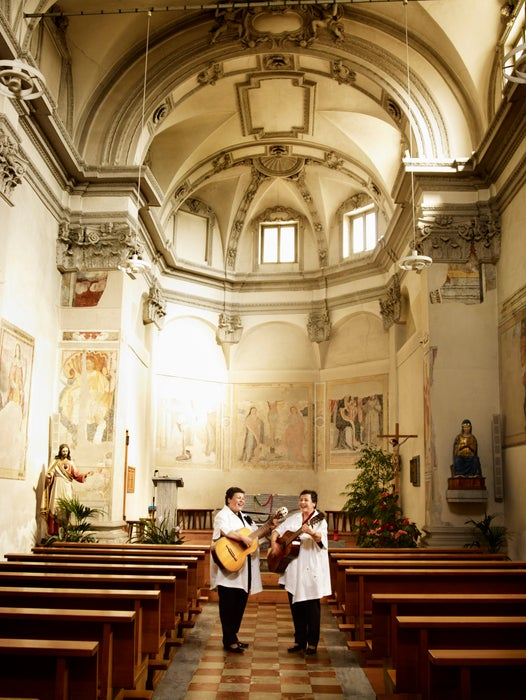 Two women singing and playing guitar in Bedigliora's church.