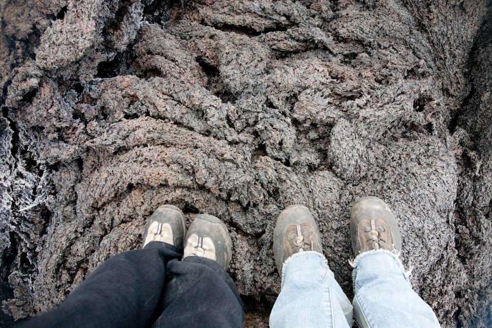 View of couple's feet standing on molten lava rock.