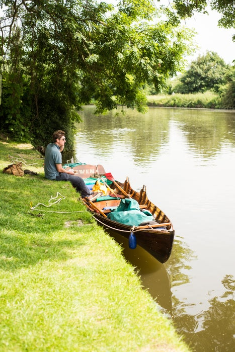 Boatman sitting on bank of River Thames with skiff boat, Walton-on-Thames.