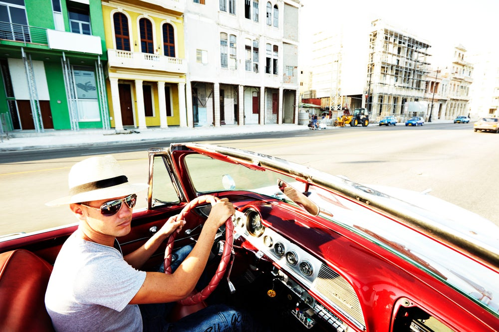 Man driving a 1950's car in Havana Cuba.