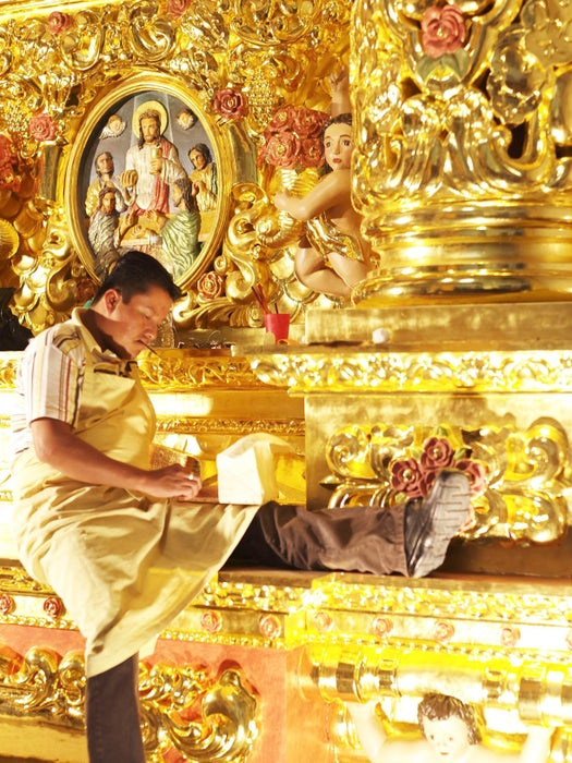 Man sitting in gold-leafed interior of Santo Domingo church.