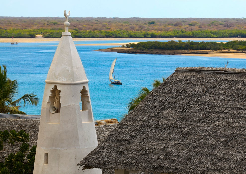 Dhow sailing between Lamu and Manda islands with minaret of Friday Mosque in foreground.