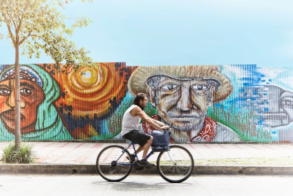 Cyclist riding past street mural.