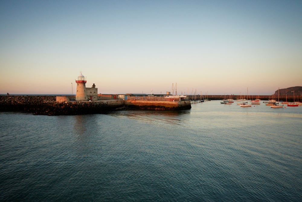 Lighthouse and fishing port at dusk.