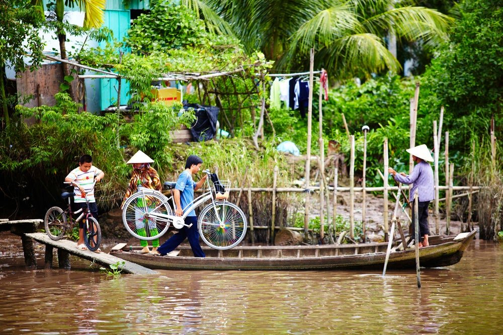 Local villagers using boat to transport bicycles across river.