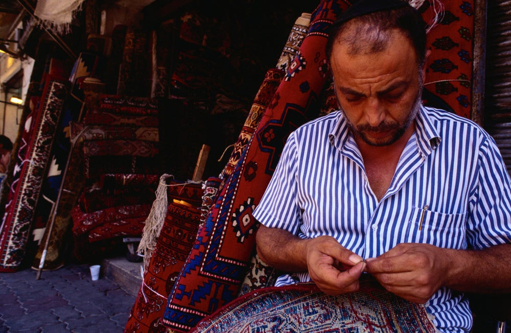 Man selling rugs in a flea market - Jaffa