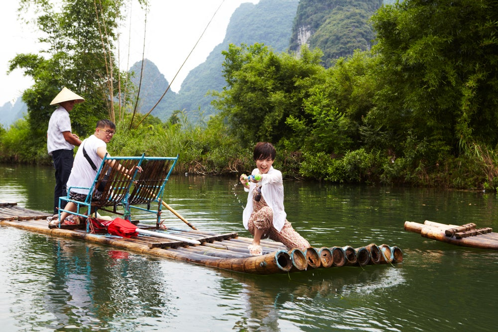 Chinese traveller on bamboo raft with water gun on Yulong River.