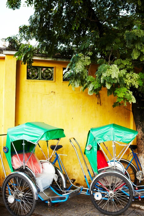 Rickshaws parked on street.