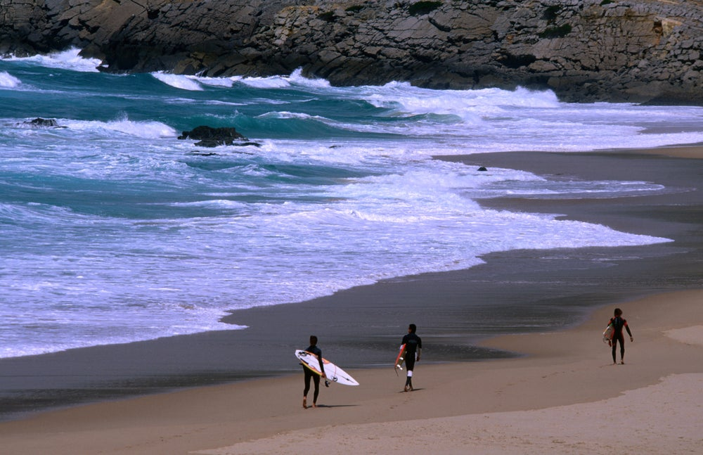 Surfers heading out to the breaks off Praia do Guincho.