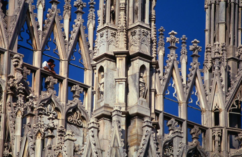Tourists standing among spires of Milan Cathedral.