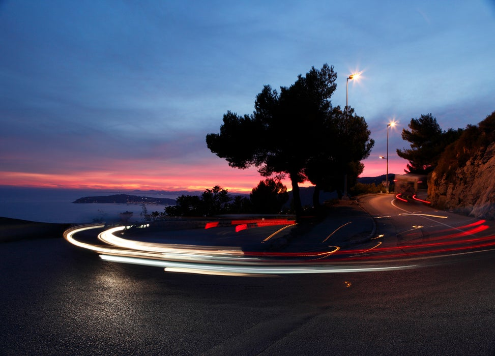 Cars turning sharp bend on D37 highway at dusk.