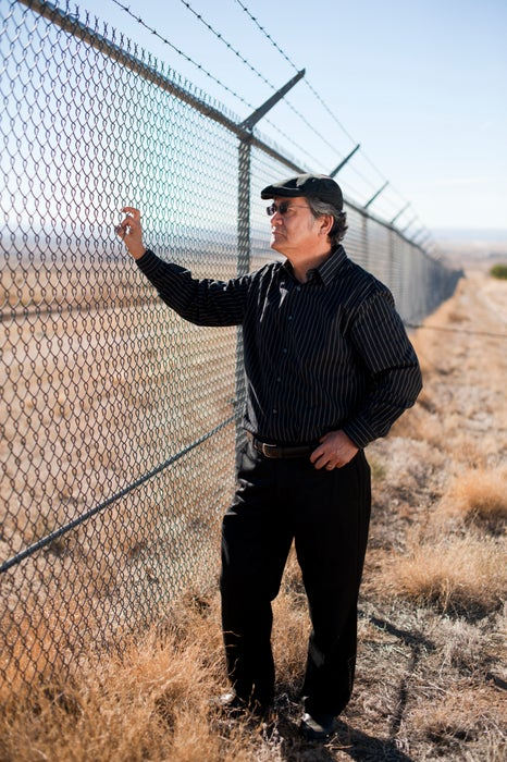 Man standing outside fence of former nuclear weapons storage facility at Manzano Base.