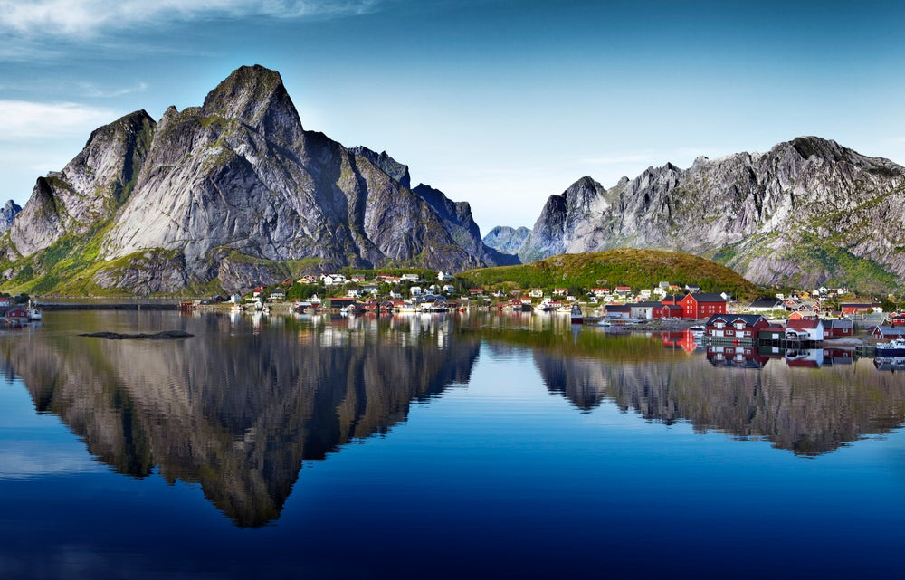 Dramatic granite peaks of Lofoten Wall and Reinebringen reflected in water beside fishing village of Reine.