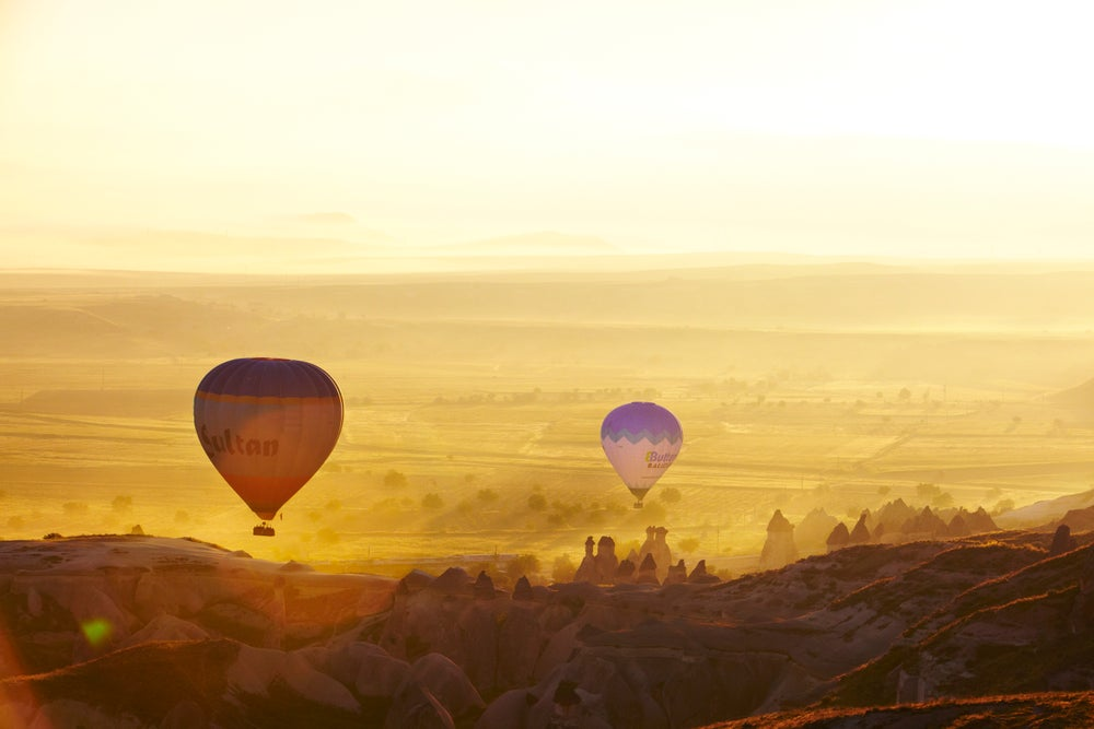 Balloons at dawn over fairy chimney rock formations.