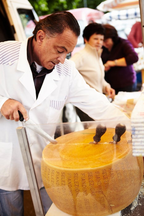 Man cutting cheese at market in Langhe Valley.