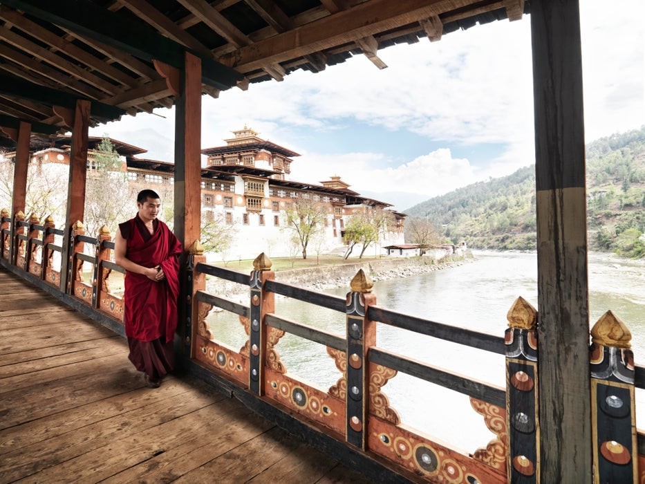 Monk walking on balcony at Punakha Dzong on junction of Pho Chhu and Mo Chhu rivers.