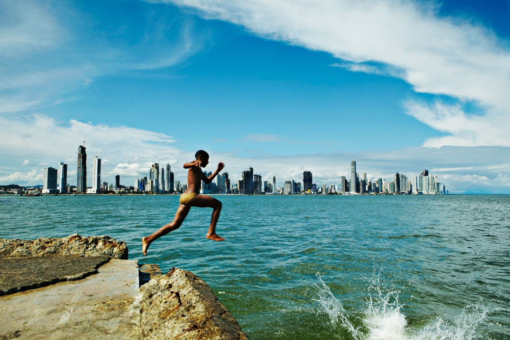 Boy jumping of rock into water in Casco Viejo bay with Panama City in background.