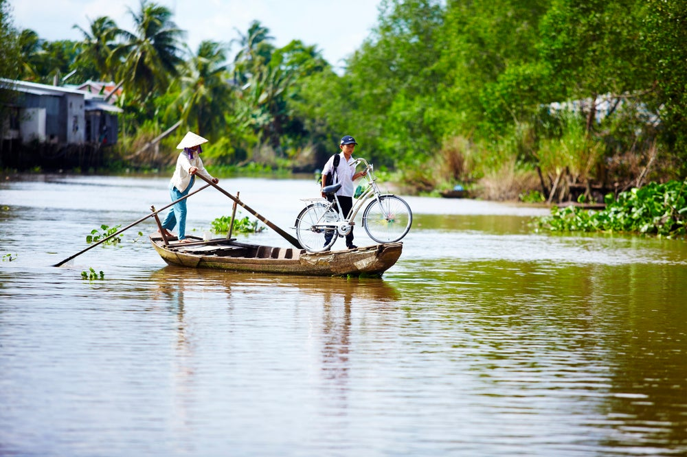Boy using boat to transport bicycle across river.