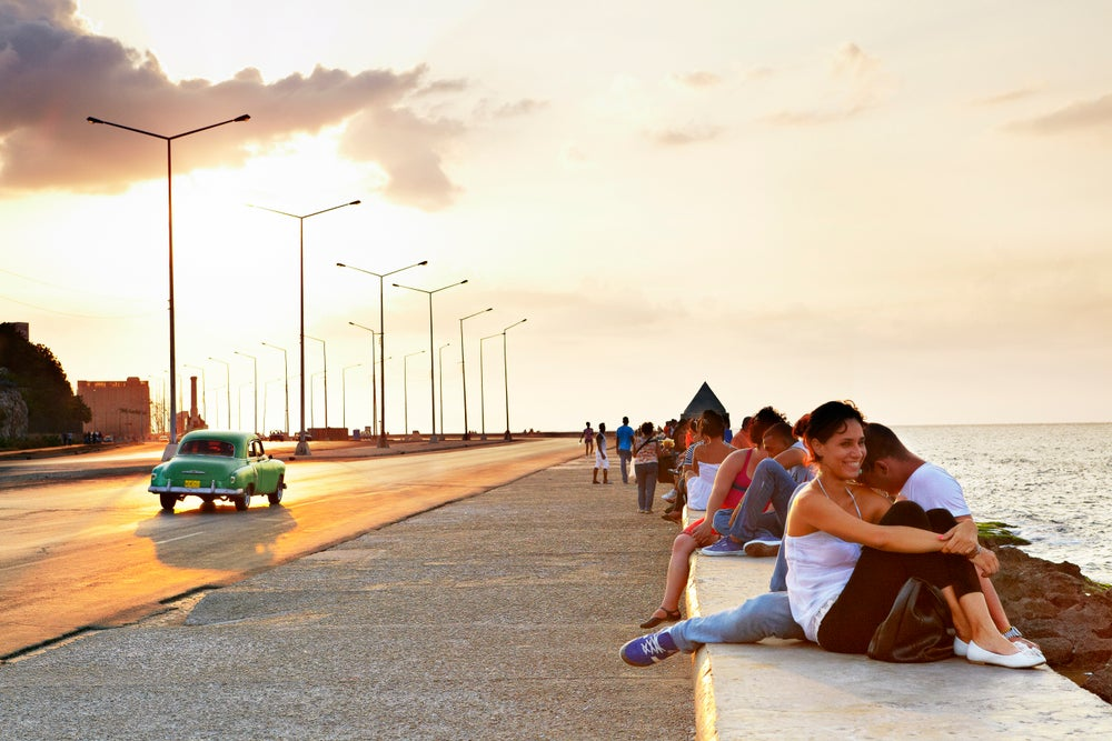People gathered beside waterfront on Malecon at sunset.