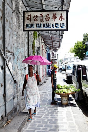 Woman walking on street in Port Louis' Chinatown near Central Market, Port Louis, Mauritius