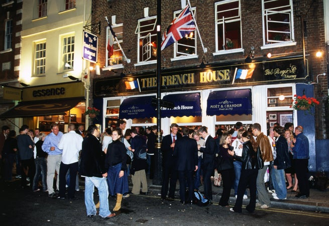 Party crowd outside French House Pub in Dean Street, Soho, London, England