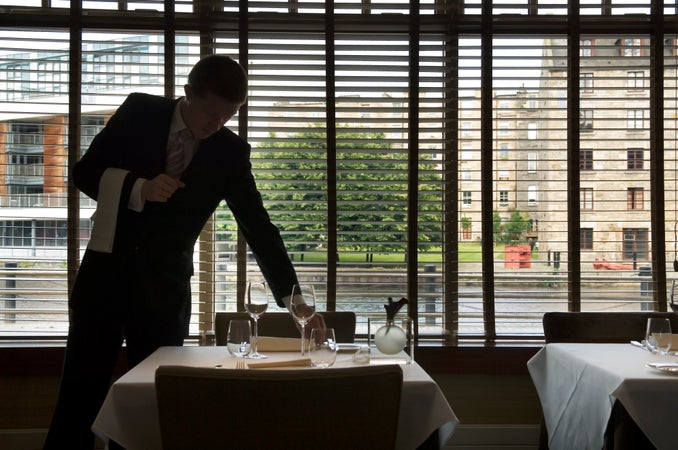 Waiter setting tables at Martin Wishart restaurant, Leith and the Waterfront, Edinburgh, Scotland