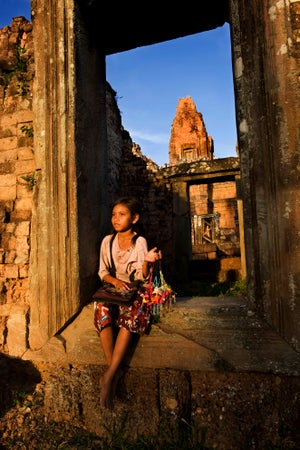 Young girl sitting in stone doorway, Pre Rup, Temples of Angkor, Cambodia