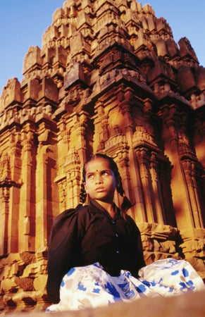 A girl sits in front of a Chalukyan ruin - Badami, Karnataka which most southern Indian temple architecture is based on, Bengaluru (Bangalore), India