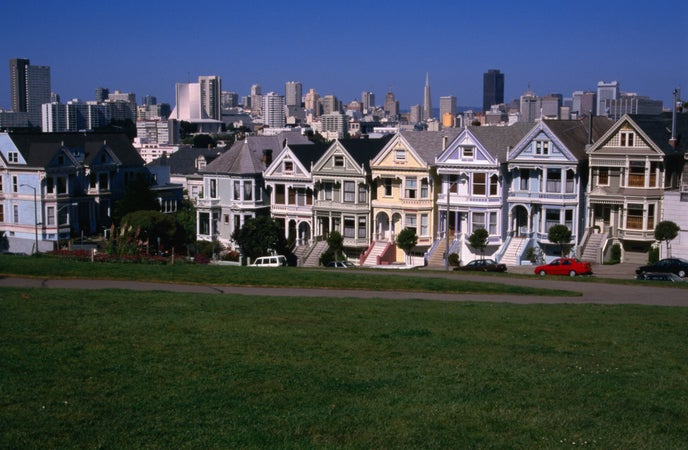 The city skyline over the rooftops of Victorian houses on Steiner Street, Alamo Square, San Francisco, USA